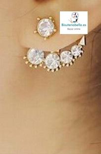 Par de pendientes dorados con perlas alrededor, brillantitos y pinchos